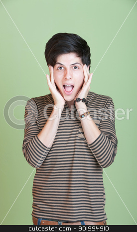 Scared Teen stock photo, Shocked Latino teen with hands on head over green background by Scott Griessel