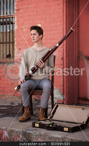 Young Bassoon Musician stock photo, Young Caucasian man with Bassoon sitting on a wooden chair outside by Scott Griessel