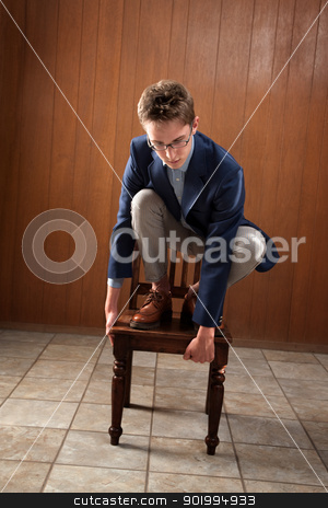 Man Stands On Chair stock photo, Young Caucasian man stands on a chair, looking down by Scott Griessel