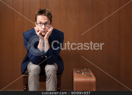 Young Man on Chair with Suitcase stock photo, Serious Caucasian male with chin in hands and suitcase by Scott Griessel