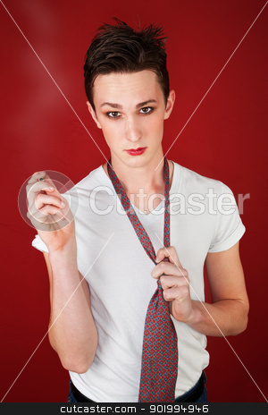 Man Holds a Cigarette stock photo, Young man on red background holds a tie and points a cigarette by Scott Griessel
