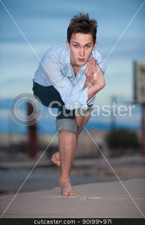 Young Man Exercising stock photo, Young Caucasian man crouches on one leg for yoga exercises outdoors by Scott Griessel