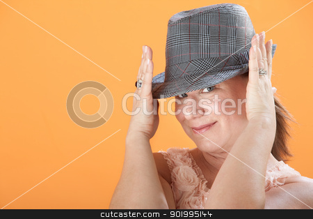 Woman Holds Her Hat stock photo, Caucasian woman on orange background adjusts hat on on her head by Scott Griessel