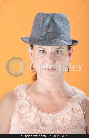 Serious Woman stock photo, Serious Caucasian woman with hat on orange background by Scott Griessel