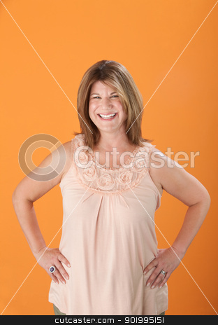 Happy Middle Aged Woman stock photo, Happy middle-aged Caucasian woman on orange background by Scott Griessel