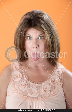 Woman Sticks Tongue Out stock photo, Mature Caucasian woman sticks her tongue out on orange background by Scott Griessel