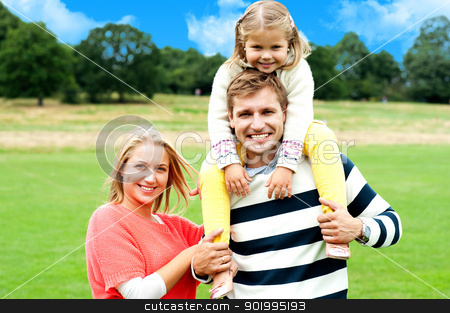 Fun loving family enjoying spring day outdoors stock photo, Little daughter on her father's shoulder having fun in park. Sunny spring day by Ishay Botbol