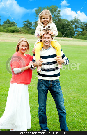 Cheerful family posing against nature background stock photo, Cheerful family posing against nature background. Full length portrait by Ishay Botbol