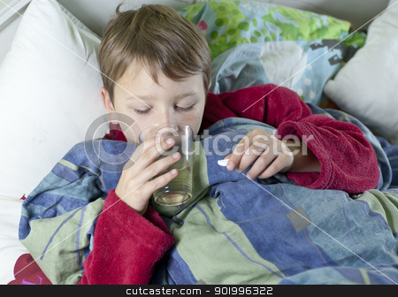 Young boy in bed taking his medicin stock photo,  Young caucasian boy in bed with the flu taking his medicin by Johan Lenell