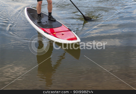 paddling stand up paddleboard stock photo, paddling stand up paddleboard on a lake - feet and legs of male paddler by Marek Uliasz