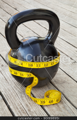 kettlebell and measuring tape stock photo, kettlebell and measuring tape on wooden deck - fitness and diet concept by Marek Uliasz