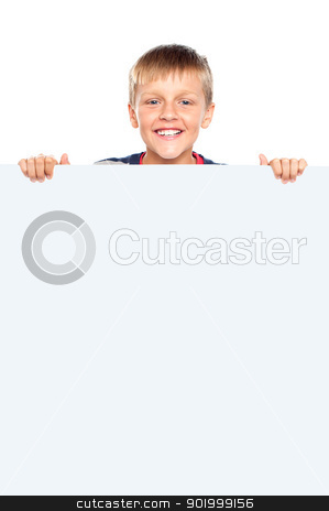 Young boy hiding behind big whiteboard ad stock photo, Young boy hiding behind big whiteboard ad. Business concept by Ishay Botbol
