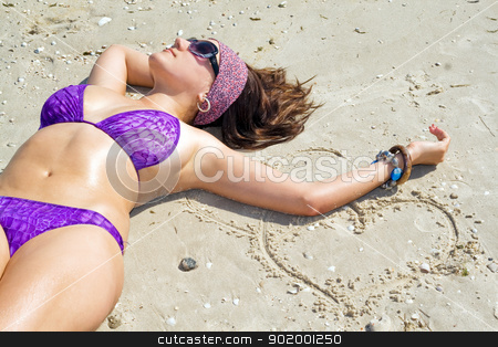 The young woman lies on sand on a beach stock photo, The young woman lies on sand on a beach by Sergii Sukhorukov