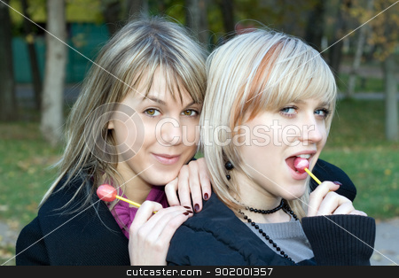 Portrait of the two young women with sugar candies stock photo, Portrait of the two young women with sugar candies by Sergii Sukhorukov