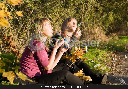 Two beauty young women starts up soap bubble in park stock photo, Two beauty young women starts up soap bubble in park by Sergii Sukhorukov