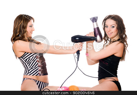 Two playful young girlfriends with hair dryers. Isolated  stock photo, Two playful young girlfriends with hair dryers. Isolated on white by Sergii Sukhorukov