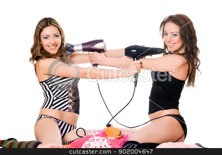 Two playful girlfriends with hair dryers. Isolated  stock photo, Two playful girlfriends with hair dryers. Isolated on white by Sergii Sukhorukov