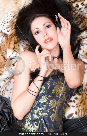 Playful young brunette in a corset stock photo, Playful young brunette in a corset posing on fur by Sergii Sukhorukov