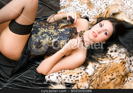 Playful young woman in a corset stock photo, Playful young woman in a corset posing on fur by Sergii Sukhorukov