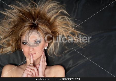Portrait of pretty young blonde stock photo, Portrait of pretty young blonde lying on the gray fabric by Sergii Sukhorukov