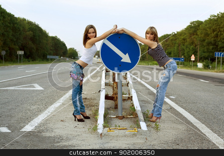Two girls stand on a road stock photo, Two girls stand on a road near the sign by Sergii Sukhorukov