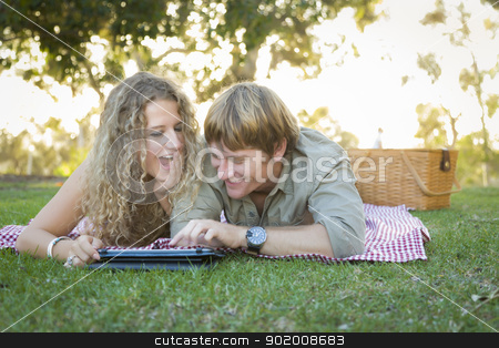 Attractive Loving Couple Using a Touch Pad Outside stock photo, Playful Loving Couple Using a Touch Pad Computer at Their Picnic Outside. by Andy Dean