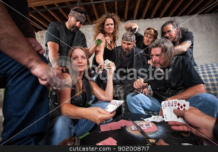 Biker Gang Lady Shows Winning Hand stock photo, Mature female biker gang member shows cards to aggressive players by Scott Griessel