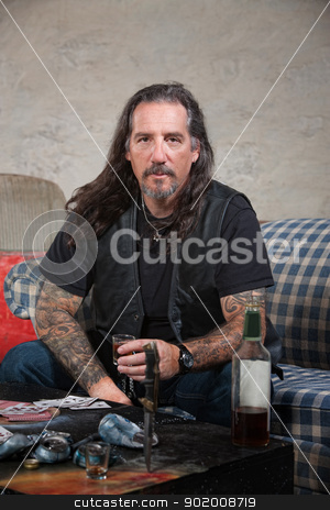 Biker Gang Member with Weapons and Alcohol stock photo, Serious biker gang member with liquor and dagger on table by Scott Griessel