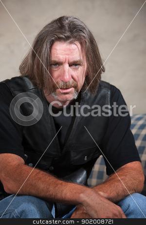 Depressed Biker Gang Member stock photo, Exhausted biker gang man sitting down indoors by Scott Griessel