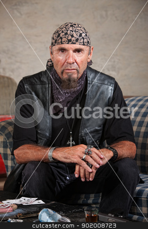 Gang Member Staring Ahead stock photo, Frowning gang member in leather vest in cold stare by Scott Griessel