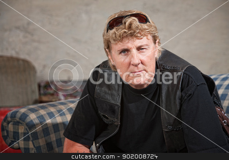 Biker Woman in Leather Vest stock photo, Aggressive white female biker gang member with sunglasses by Scott Griessel