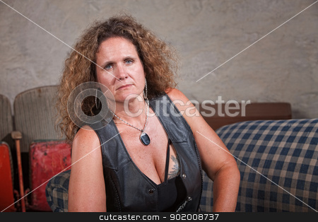 Serious Mature Woman stock photo, Serious mature biker woman in leather vest sitting indoors by Scott Griessel