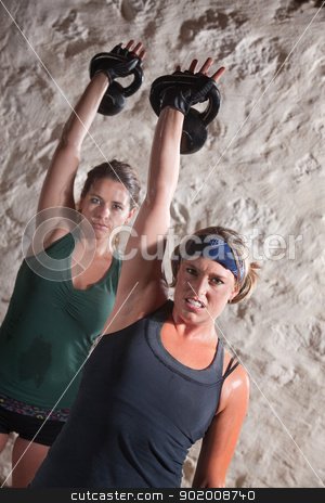 Ladies Doing Boot Camp Style Workout stock photo, Strong ladies pushing up kettle bell weights during boot camp workout by Scott Griessel
