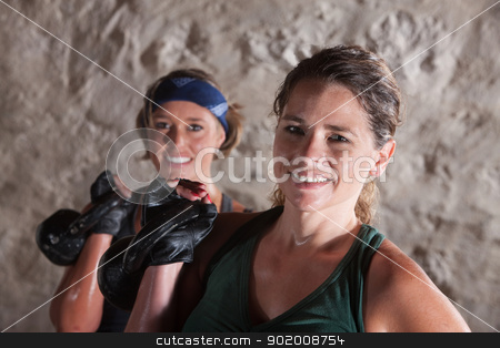 Smiling Ladies Holding Kettlebells stock photo, Pair of smiling ladies holding kettlebell weights by Scott Griessel