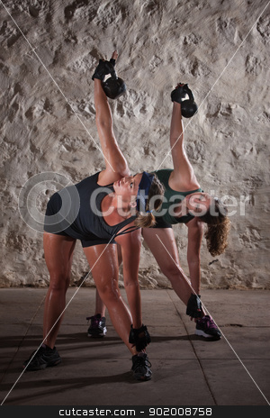 Women Doing Boot Camp Workout stock photo, Pair of pretty women lifting kettlebell weights over their shoulders by Scott Griessel