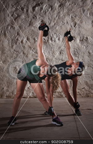 Ladies Doing Boot Camp Workout stock photo, Two pretty ladies women lifting kettlebell weights over their shoulders by Scott Griessel