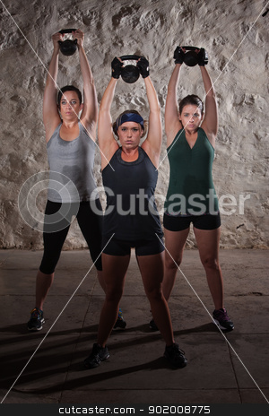 Sweating Women Doing Boot Camp Exercises stock photo, Strong females pushing kettle bell weights over their heads by Scott Griessel
