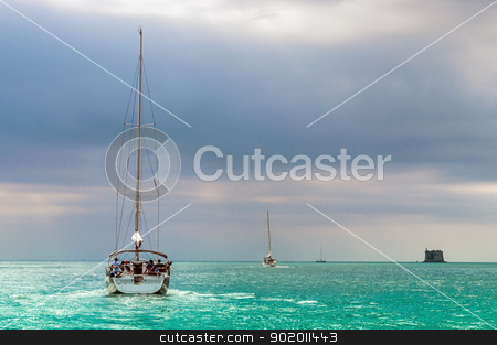 Sailing boat in a azure sea stock photo, Sailing boat in azure sea in a bad weather sky by Alberto Rigamonti
