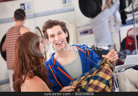 Young Couple in the Laundromat stock photo, Handsome young Caucasian man with girlfriend smiles in the laundromat by Scott Griessel