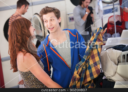 Laundromat Flirt stock photo, Young handsome Caucasian man flirts with beautiful lady in laundromat by Scott Griessel