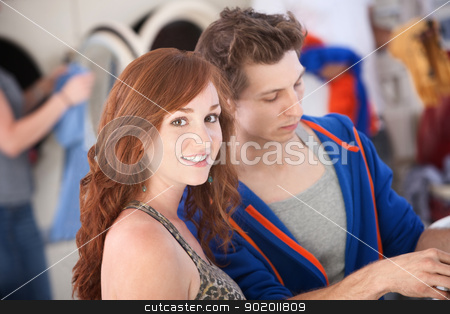 Woman in Laundromat stock photo, Beautiful woman with boyfriend smiles in the laundromat by Scott Griessel