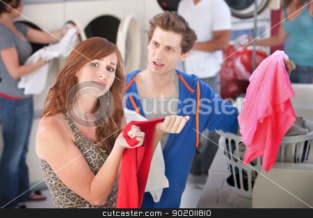 Dyed Clothing Problem stock photo, Upset man and woman with stained clothes in laundromat by Scott Griessel