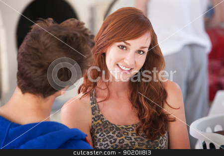 Beautiful Smiling Woman  stock photo, Beautiful young Caucasian lady with boyfriend smiles in laundromat by Scott Griessel