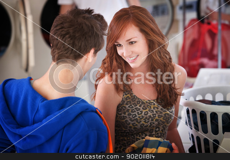 Flirting Laundromat Couple stock photo, Gorgeous young Caucasian lady flirts with a man in laundromat  by Scott Griessel