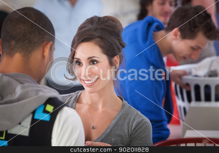 Smiling Woman In Laundromat stock photo, Beautiful Caucasian woman smiles at a guy in the laundromat by Scott Griessel