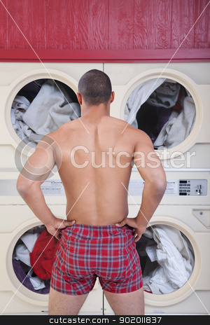 Muscular Man In Laundromat stock photo, Muscular man in boxer shorts waits in front of washing machines by Scott Griessel