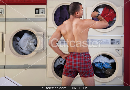 Half-naked Man in Laundromat stock photo, Muscular man in boxer shorts looks at wristwatch in laundromat by Scott Griessel
