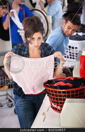 Woman Holding Granny Panties stock photo, Worried young lady holds oversize granny panties in laundromat by Scott Griessel