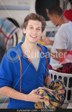 Smiling Man In Laundromat stock photo, Handsome man folds a plaid shirt in the laundromat by Scott Griessel