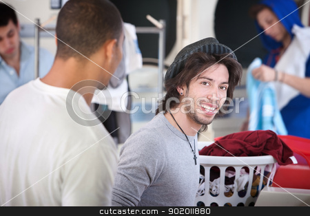 Man in Laundromat stock photo, Young handsome man with his friend smiles in the laundromat  by Scott Griessel